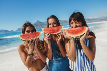 Young women having fun on the beach and eating watermelon