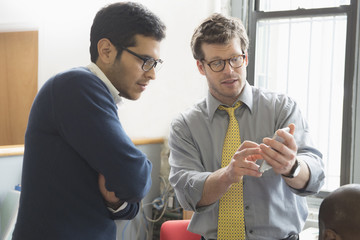 Businessmen texting on cell phone in office