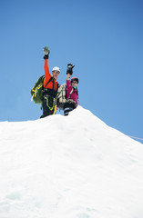 Couple waving on snowy mountain, Everest, Khumbu region, Nepal