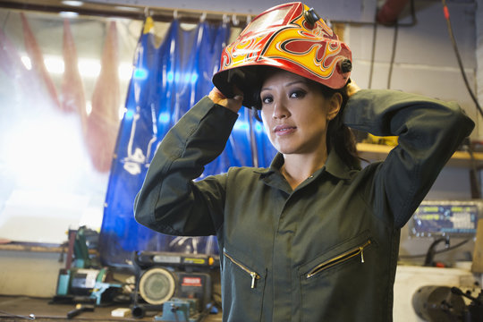 Mixed Race woman wearing protective mask in workshop
