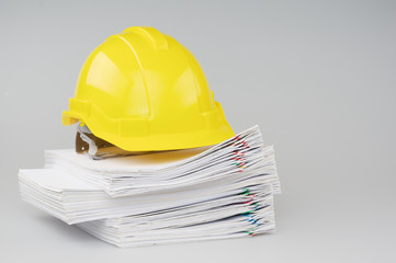 Pile overload document have yellow engineer hat on top
