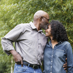 Black man kissing wife on forehead outdoors