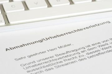 Ein Computer und eine Abmahnung wegen Urheberrechtsverletzung nach einem Streaming