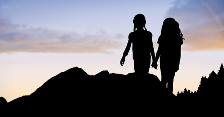 Silhouette girls holding hands on mountain against sky