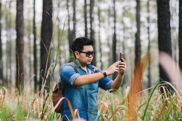 A man with his mobile smart phone searching for reception signal in the forest.