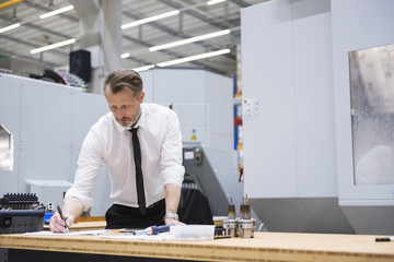 Man at table in factory shop floor taking notes
