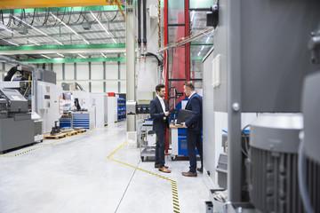 Two businessmen in factory shop floor