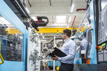 Man with documents standing among machines in factory shop floor