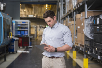 Man using tablet in factory warehouse