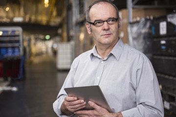 Man holding tablet in factory warehouse
