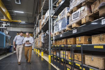 Two men with tablet walking in factory warehouse