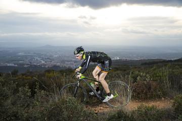 Cyclist man riding mountain bike on mountain.