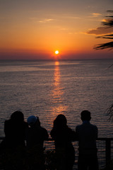 silhouette of people watching beautiful sunset by the sea