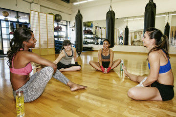 Women sitting in circle on floor of gymnasium stretching legs