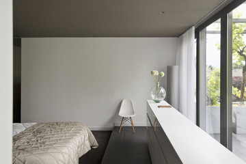 View of a cropped bed along large window in bedroom at contemporary house