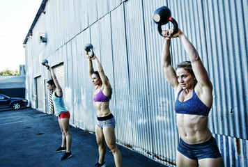 Women lifting kettlebells outdoors
