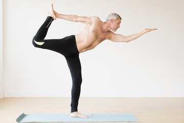Older Caucasian man doing yoga on exercise mat