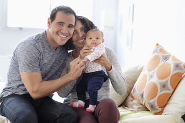 Hispanic mother and father posing with baby daughter