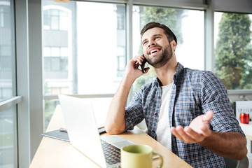 Cheerful man in office talking by phone