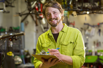 Smiling Caucasian worker writing on clipboard in bicycle shop
