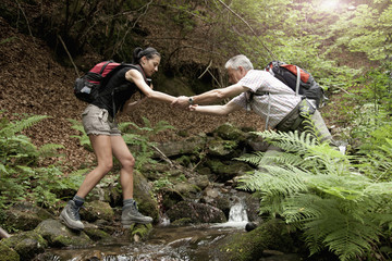 Caucasian man helping woman crossing forest river