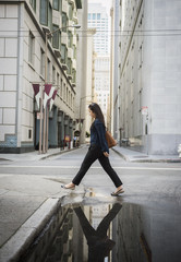Reflection in puddle of Chinese businesswoman crossing street