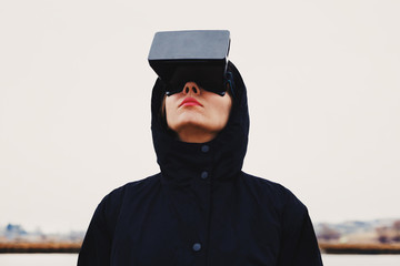 Woman wearing virtual reality goggles in the outdoors
