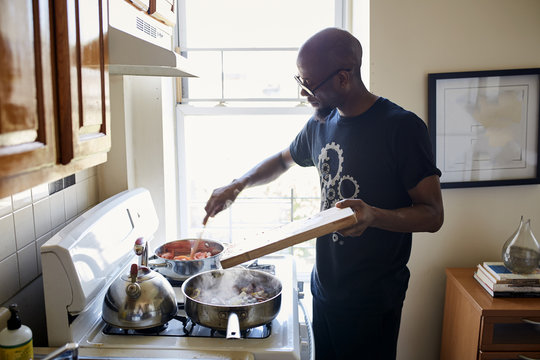 Black man holding cutting board cooking on stove