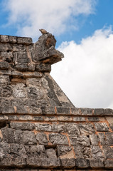 A lizard sits on top of an antique statue of Kukulcan at Chichen Itza, Mayan Ruins, Yucatan, Mexico. detail at the Ossuary or the Temple of High Priest.