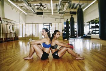 Women sitting back to back on floor of gymnasium