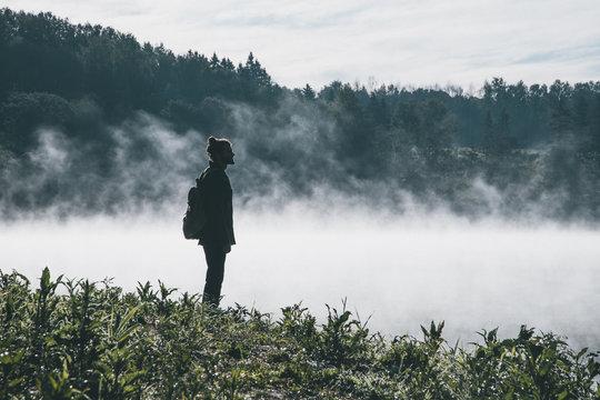 Man standing in foggy landscape
