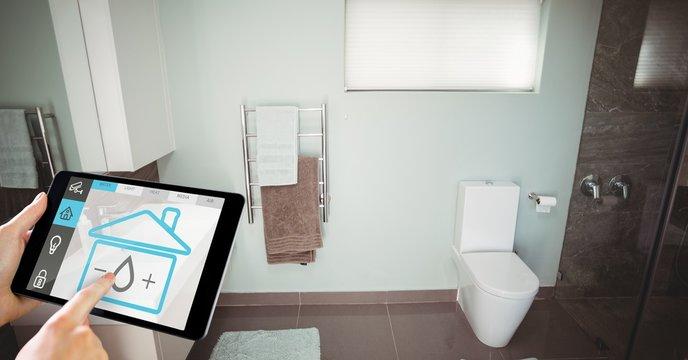 Hand using smart home application on digital tablet in washroom