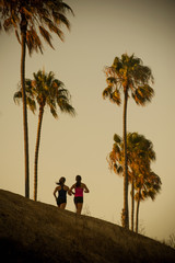 Women jogging by palm trees