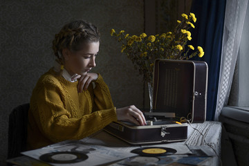 Woman playing vinyl records on portable turntable