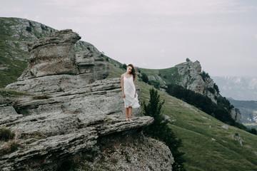 Caucasian woman standing on rock overlooking landscape