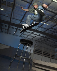 Caucasian man jumping on skateboard over stool indoors