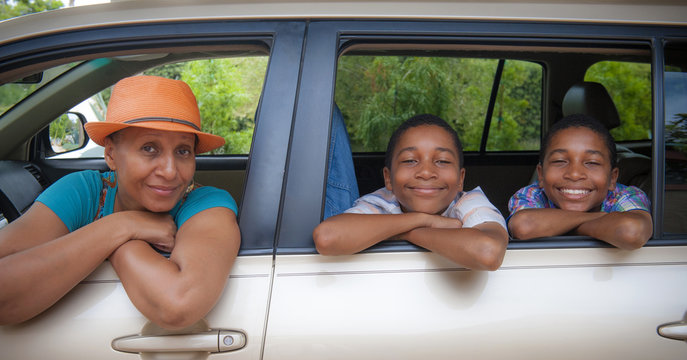 Portrait of mother and twin sons leaning on car windows