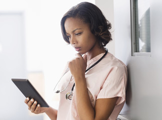 Mixed Race nurse using digital tablet leaning on door