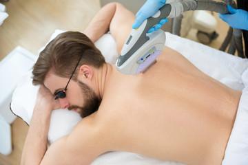 Beautician giving men laser epilation