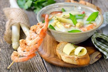 Spargelcremesuppe mit Garnelen und Zuckerschoten, mit getoastetem Butterbaguette rustikal serviert - Cream of asparagus soup with fried prawns and snow peas