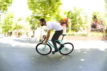 Cyclist man riding fixed gear sport bike in sunny day on a city