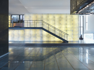 Open lobby with staircase in front of illuminated wall
