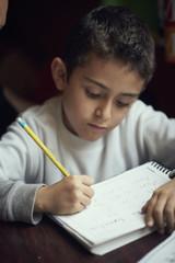Hispanic boy practicing writing alphabet