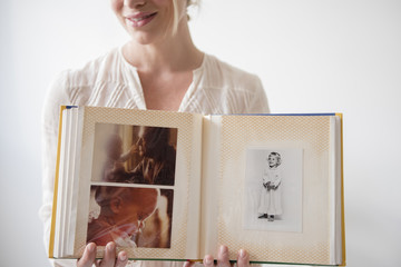Caucasian woman showing photo album