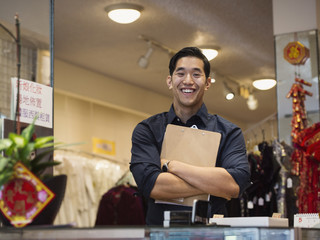 Smiling Chinese man posing with clipboard in store