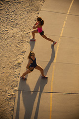 Mixed Race mother and daughter stretching on path at beach