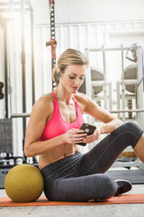 Woman sitting with heavy ball in gymnasium listening to cell phone