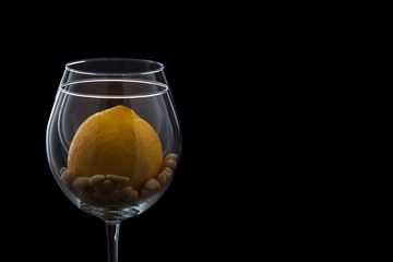 a glass on a black background, peanut and lemon, the contour of the glass with lemon and peanuts. the theme of healthy eating, lemon water and peanuts.