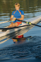 Caucasian man rowing on river