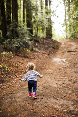 Caucasian girl walking on forest path